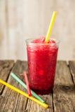 Slushie vermelho congelado no copo plástico com palha imagens de stock royalty free