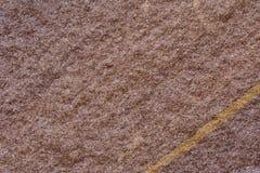 Slut av rödbrun stenyttersida med den guld- linjen bortgång till och med a Arkivfoton