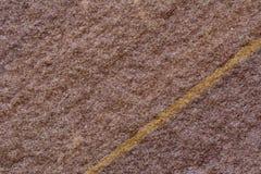 Slut av rödbrun stenyttersida med den guld- linjen som igenom klipps som th Royaltyfria Foton