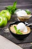 Slut för bästa sikt upp den Apple smulpajefterrätten med vaniljglass, grön mintkaramell på den gråa trätabellen gaffel med kakan  Royaltyfria Foton
