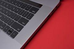Slut för grå färgmetallbärbar dator upp usb-typ c på röd bakgrund arkivbild