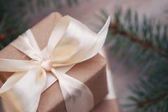 Slut för julgåvaask upp med granfilialer och kottar på träbakgrund, kopieringsutrymme Dekorerad julgåva Royaltyfri Bild