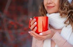 Slut för kopp för kvinnainnehavvinter upp på röd bakgrund arkivfoto