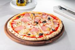 Slut för selektiv fokus upp läcker köttpizza med bacon, den fega filén, skivade champinjoner och oliv på träbrädet på set Arkivbild