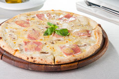 Slut för selektiv fokus upp läcker pizza med bacon, skivade champinjoner och gräddost på träbrädet på den tjänade som restauranen Arkivfoto