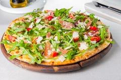 Slut för selektiv fokus upp läcker pizza med skivor för hamon och för körsbärsröd tomat, parmezan ost och arugula på träbrädet på Royaltyfri Foto