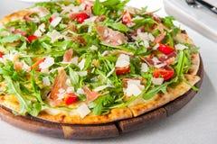 Slut för selektiv fokus upp läcker pizza med skivor för hamon och för körsbärsröd tomat, parmezan ost och arugula på träbrädet på Arkivfoto