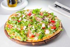 Slut för selektiv fokus upp läcker pizza med skivor för hamon och för körsbärsröd tomat, parmezan ost och arugula på träbrädet Royaltyfri Foto