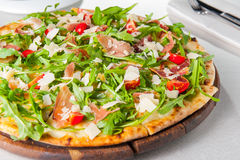 Slut för selektiv fokus upp läcker pizza med skivor för hamon och för körsbärsröd tomat, parmezan ost och arugula på träbrädet Royaltyfri Bild
