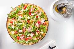 Slut för selektiv fokus upp läcker pizza med skivor för hamon och för körsbärsröd tomat, parmezan ost och arugula på träbrädet på Royaltyfri Fotografi