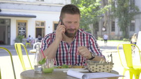 Slut för ung man kallar och blickar på kameran, under lunch lager videofilmer