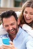 Slut som skrattar upp par som tillsammans sitter i omfamning med mobiltelefonen Arkivfoton