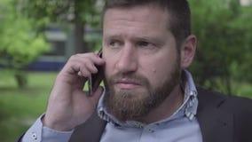 Slut upp affärsmanframsidan som talar vid smartphonen som är utomhus-, pannaskott lager videofilmer