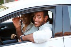 Slut upp afrikansk amerikanparsammanträde, i att le för bil arkivfoto