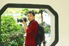 Slut upp arbete för kamera för håll för Aisan kinesiskt manfotograf i natur royaltyfria foton