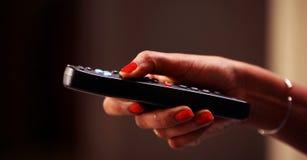 Slut upp av ändrande kanaler för TVfjärrkontroll och volymförhöjning, hållande ögonen på TV för tonårs- flicka i vardagsrummet el royaltyfria foton