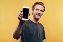 Slut upp av att le mannen som rymmer Smartphone royaltyfri fotografi