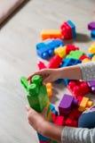 Slut upp av barnhanden som spelar med plast- konstruktionskvarter Framkallande leksaker tidigt lära Liten flickabyggande Arkivbilder