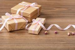 Slut upp av beigea hantverkgåvaaskar med det rosa silkeslena bandet på en träbakgrund, kopieringsutrymme royaltyfri foto