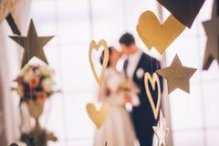 Slut upp av bröllopgarneringar Fokus på garneringar Brud och brudgum i bakgrund Arkivbilder
