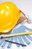 Slut upp av byggmästares hjälpmedel - hjälmen, arbetshandskar, hammare, skriver a Royaltyfri Fotografi