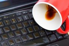 Slut upp av coffedroppe och en röd kopp av coffe över bärbara datorn, våt skadeflytande och spillet på tangentbordet, olycksbegre Fotografering för Bildbyråer