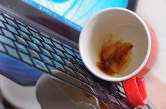 Slut upp av coffedroppe och en röd kopp av coffe över bärbara datorn, våt skadeflytande och spillet på tangentbordet, olycksbegre Arkivbilder