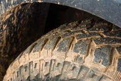Slut upp av däckmönstergummihjulet 4x4 av vägen, textur av den smutsiga hjulhackan Arkivfoto