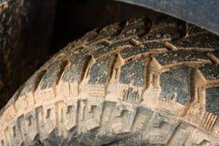 Slut upp av däckmönstergummihjulet 4x4 av vägen, textur av den smutsiga hjulhackan Arkivbild