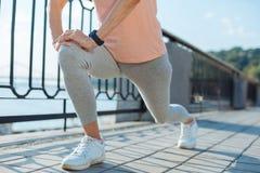 Slut upp av den äldre kvinnan som gör utfall, innan att jogga Royaltyfri Fotografi