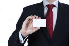 Slut upp av den bärande dräkten för affärsman som rymmer det tomma kortet på vit Royaltyfri Foto