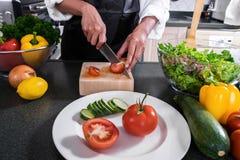 Slut upp av den bitande tomaten för kvinnahand på att hugga av wood brädeintelligens Arkivfoto