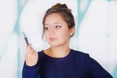 Slut upp av den härliga unga kvinnan som rymmer en eyeliner i hennes hand, i en suddig bakgrund royaltyfri foto
