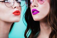 Slut upp av den halva framsidan av två härliga kvinnor med ljusa kanter på blå bakgrund Skönhetsmedel läppstift, kantglans Royaltyfri Fotografi