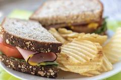 Slut upp av den hela vetesmörgåsen med potatischiper på sida Royaltyfri Bild