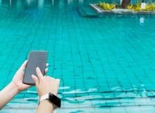 Slut upp av den kvinnliga handinnehavSmart mobiltelefonen med den tomma skärmen och den bärande smarta klockan på simbassäng av d Arkivbild