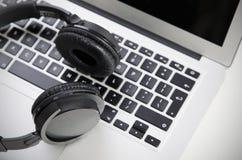 Slut upp av den ljudsignal hörlurar med mikrofon på bärbara datorn Arkivbilder