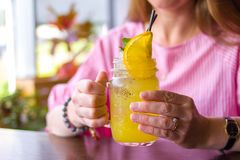 Slut upp av den lyckliga kvinnan som dricker den gula coctailen med den orange skivan på kafét - drinkar, folk och livsstilbegrep royaltyfri bild