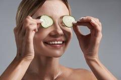 Slut upp av den lyckliga kvinnan som sätter stycken av gurkor på hennes ögon arkivfoton