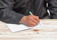 Slut upp av den mänskliga handen med pennan på trätabellen arkivfoton