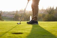 upp av den manliga golfaren som ställer upp putt på gräsplan Royaltyfri Foto