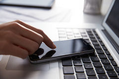 Slut upp av den Person At Laptop Using Mobile telefonen Arkivbilder