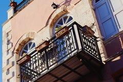 Slut upp av den rosa husväggen med balkongen och blommor royaltyfri foto