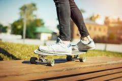 Slut upp av den unga mannen i gymnastikskor som rider longboard eller skateboarden i parkera royaltyfri bild
