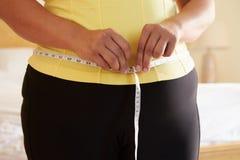 Slut upp av den överviktiga kvinnan som mäter midjan Royaltyfria Bilder