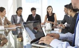 Slut upp av det affärsmanUsing Laptop During styrelsemötet omkring arkivbild