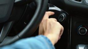 Slut upp av det kvinnliga fingret som trycker på en knapp för motorstartstopp i bil stock video