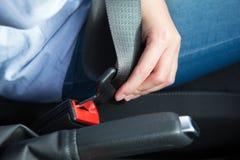Slut upp av det Person In Car Fastening Seat bältet royaltyfria bilder
