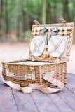 Slut upp av en öppen picknickkorg över trätabellen i parkera Royaltyfria Bilder