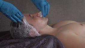 Slut upp av en ansikts- massage för stiligt häleri för ung man på brunnsortmitten arkivfilmer